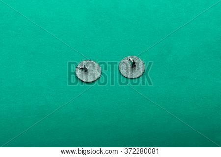 Gray Push Pins On A Green Textured Background With Soft Focus