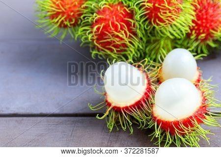 Fresh Rambutan Peeled On Wood Table With Bunch Of Fresh Ripe Rambutan Background. Tropical Fruit Fre