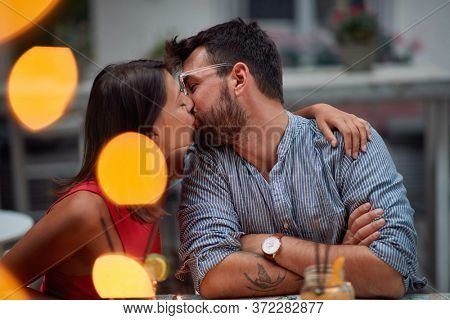 Young handsome couple in an intimate kiss in romantic atmosphere