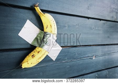 Yellow Banana Duct-taped To A Blue Wooden Wall - Concept Of Potassium And Healthy Lifestyle With Sea