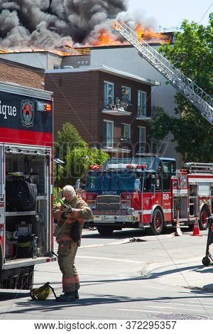 MONTREAL, CANADA - JUNE 18, 2020:  Firefighter puts on his firefighter equipment before facing a fire in a residential building in Montreal, Canada