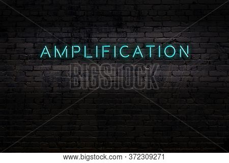 Neon Sign With Inscription Amplification Against Brick Wall. Night View