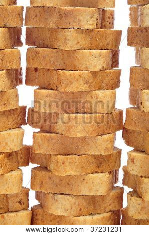 some piles of whole-wheat mini toasts on a white background poster