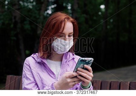 Redhead Girl In Medicine Mask Reading News From Smartphone In The Park During Coronavirus Revival