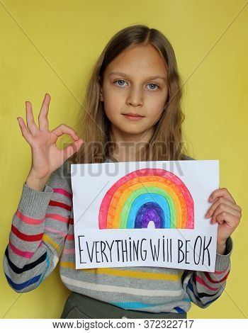 A Blonde Preteen Girl On Yellow Background Holds A Sheet Of Paper. She Drew A Rainbow And Wrote Phra