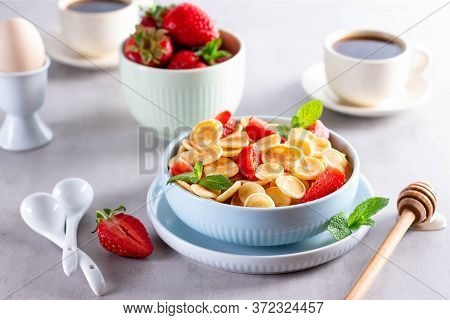 Trendy Food - Pancake Cereal. Heap Of Mini Cereal Pancakes In Bowl. Tiny Baked Pancakes With Honey A