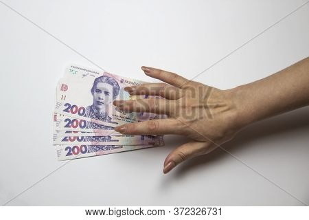 Female Hand Want To Touch A Thousand Hryvnia. Ukrainian Currency With Woman's Hand Against Backgroun