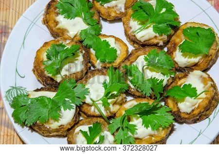 Sliced ​​fried Zucchini With Mayonnaise And Parsley.