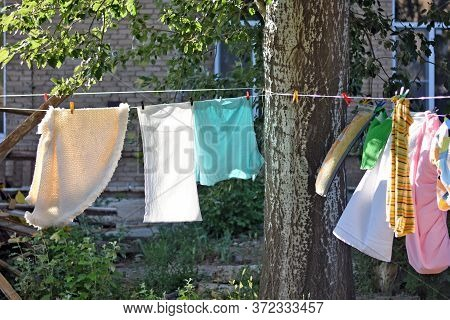 Multi-colored Linen Is Dried On A Clothesline On The Street. Clothesline Stretched Between Trees
