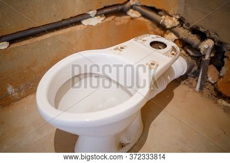 Installing A New Toilet In The Bathroom During Repair Work. Bathroom During Finishing Work. Installa