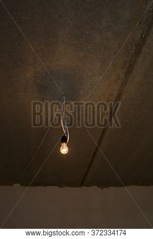 Light Bulb On The Ceiling. Lonely Light Bulb And Wire Sticking Out Of The Ceiling During A Repair