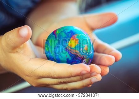 Conceptual Photo of a Saving the Planet, Babie's Hands Holding Little Earth, Made of Plasticine, Future of the Planet, Pollution Free.
