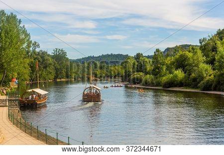 La Roque-Gageac, Dordogne, France - August 13, 2019: Boats on the river Dordogne at La Roque-Gageac. France