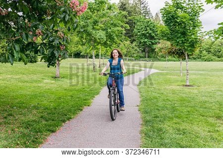 Pregnant Woman In The Green Park Riding Bicycle.