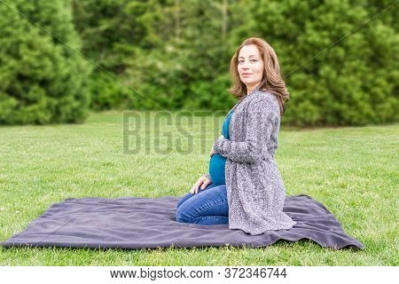Happy Pregnant Caucasian Woman Relaxing In A Park Holding Hands On Her Belly.