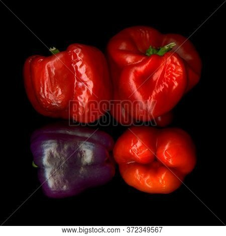 Four withered bell peppers view from above