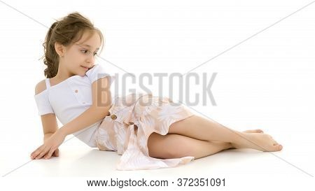 Beautiful Girl Lying On The Floor Against White Background, Portrait Of Adorable Preteen Barefoot Gi