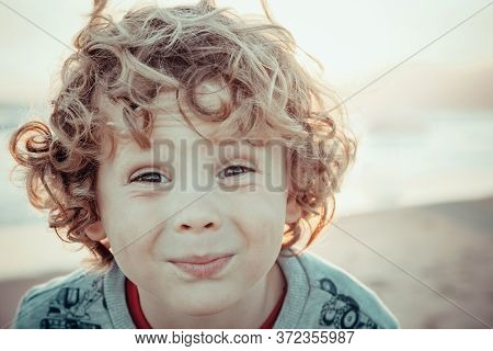 Portrait Of A Charming Blond Child With Large Curls In Sunset Light On The Beach. The Concept Of Hap