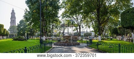 A Fountain In The Plaza De Armas In Morelia, With The Cathedral On The Background, In The Mexican St