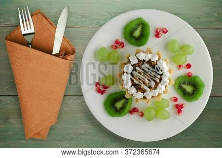 Dessert Of Cake And Fruit Grapes, Kiwi, Pomegranate On A Green Wooden Background. Dessert On A Wheit