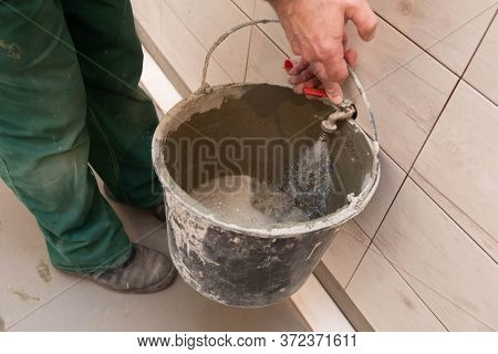 Construction Worker. Unscrewed Tap. Tap Water Flows Into The Bucket. During Renovation. Tiles On The