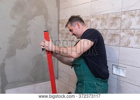 Red Spirit Level. Washes Measuring Tools With A Wet Cloth. Middle-aged Manual Worker. General Constr