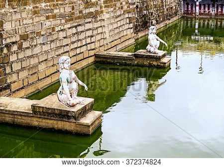 Two Ancient Statues - A Woman And A Man, On Ledges In The Wall Of An Old Pond Near Indian Temple