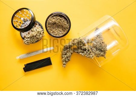 Joint Weed. The Pot Leaves On Buds. Thc Cbd. Yellow Background. Cannabis Weed Bud And Grinder.