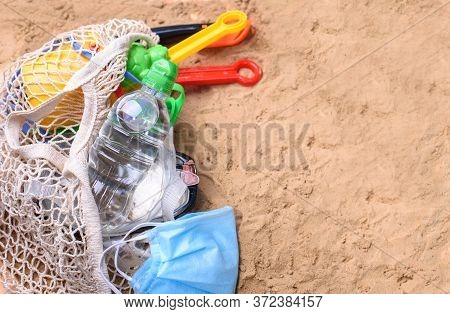 Beach Sand With Toys For The Baby, Water, The Word Holi Stay In Colored Letters.