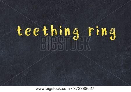 Chalk Handwritten Inscription Teething Ring On Black Desk