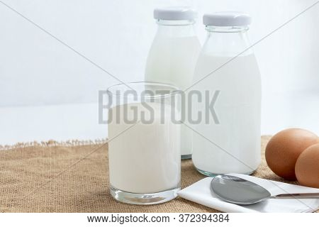 Bottle Of Milk With A Glass Of Milk And Eggs On The Sackcloth With White Background. Healthy Food Fo