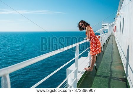 A Woman Is Sailing On A Cruise Ship, A Girl Is Standing Near The Fence On A Ship And Looking At The