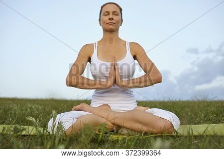 Yoga Woman Meditation In Nature. Athletic Woman In White Clothes Meditates In Lotus Position On The