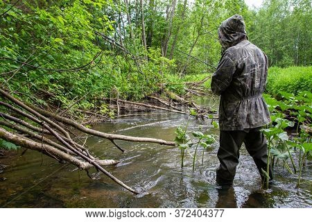 A Fisherman With A Spinning Rod In His Hands Catches Fish On A Small Forest River With Lots Of Snags