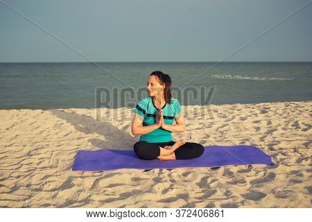 Beautiful Brunette Woman With Ponytail Sit In Yoga Lotus Padmasana Pose With Namaste Hands Position,