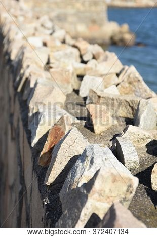 Jagged Retaining Wall With Rough Rocks Along The Top Edge.