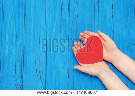 Top View Of Childs Hands Holding Red Heart Over A Wooden Background. Health Care, Love And Pediatric