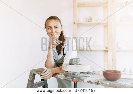 A Businesswoman In Her Pottery Shop. A Girl At Work With Clay In A Pottery Workshop.