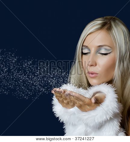 Attracive girl in santa cloth blowing snow from hands