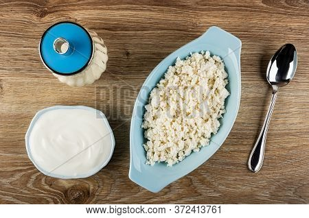 Sugar Bowl, Glass Bowl With Sour Cream, Grainy Cottage Cheese In Blue Oval Bowl, Spoon On Wooden Tab