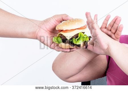 Asian Obese Women Show Signs Of Rejection Hamburger With The Person Who Submits It, On White Backgro