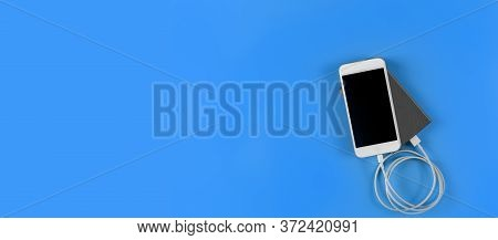 Top View Smartphone Charging With Power Bank On Blue Background With Copy Space. Smartphone Charging