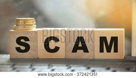 Word Scam. Wooden Small Cubes With Letters Isolated On Computer Keyboards With Copy Space Available.