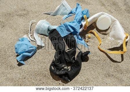 Virus Mask And Plastic Gloves, Disposable Medical Garbage On Sea Coast, Coronavirus Covid Pollution
