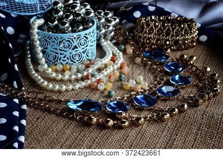 Jewelry In A Box. Jewelry Bead, Earrings Chains On A Brown Sack Background. Design, Fashion And Styl