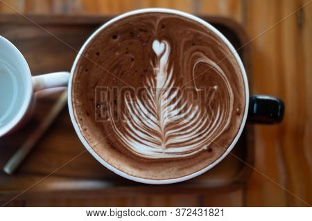 Delicious Hot Chocolate With Froth Art On Top Of Wooden Table