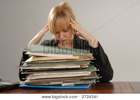 Stressed Businesswoman With Pile Of Files