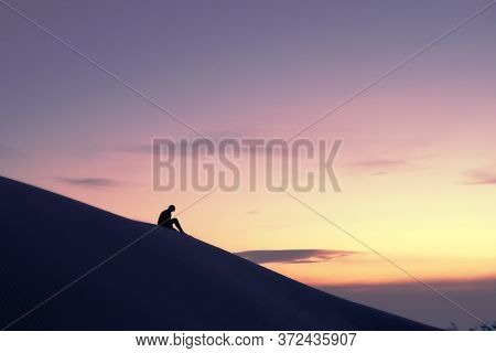 Woman Silhouette Contemplating The Horizon In The Desert From Atop A Dune Against A Golden Sky At Su