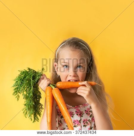 Nice Little Girl In Summer Dress With Flower Pattern And Band On Hair Biting Carrot With Appetite. C