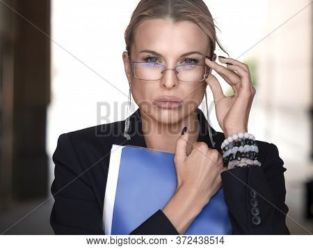 Businesswoman Or Lawer Tightly Holds The Document Folder, Adjusts Her Eyeglasses And Incredulously L
